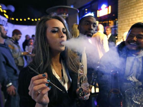 Jovem fuma maconha em uma festa de Réveillon que celebra o início da venda da droga em Denver
